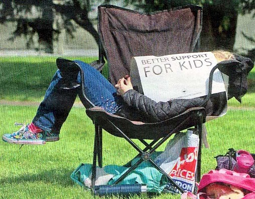 Power Nap and Pwer Struggle: A Child uses a strike sign for shade while her mom walks a picket line outside school in Vancouver. Photo credit Darryl Dyck / The Canadian Press via Vancouver Metro