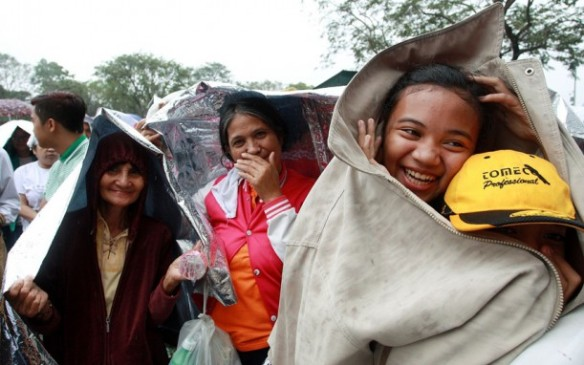 Pilgrims gather in the rain at Rizal Park to experience Sunday Mass with Pope Francis. Picture: GETTY