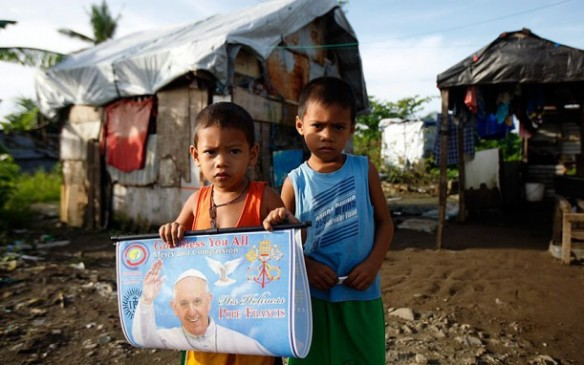 Filipino children hold a portrait of Pope Francis in village which was severely damaged by the 2013 Typhoon Haiyan in Tacloban City, Leyte province. Picture: EPA/JAY LABRA