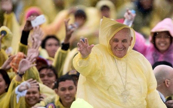 Pope Francis wears a plastic poncho as he waves to well wishers after a mass in Tacloban, Picture: JOHANNES EISELE/AFP/Getty Images